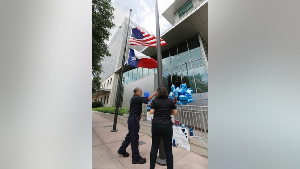 Flags are lowered to half-staff at the San Antonio Police headquarters, Friday, June 30, 2017, in San Antonio. San Antonio police Officer Miguel Moreno died Friday of wounds suffered when he and his partner were shot by a man they intended to question about a vehicle break-in Thursday. The suspect was killed in the shootout. (AP Photo/Eric Gay)
