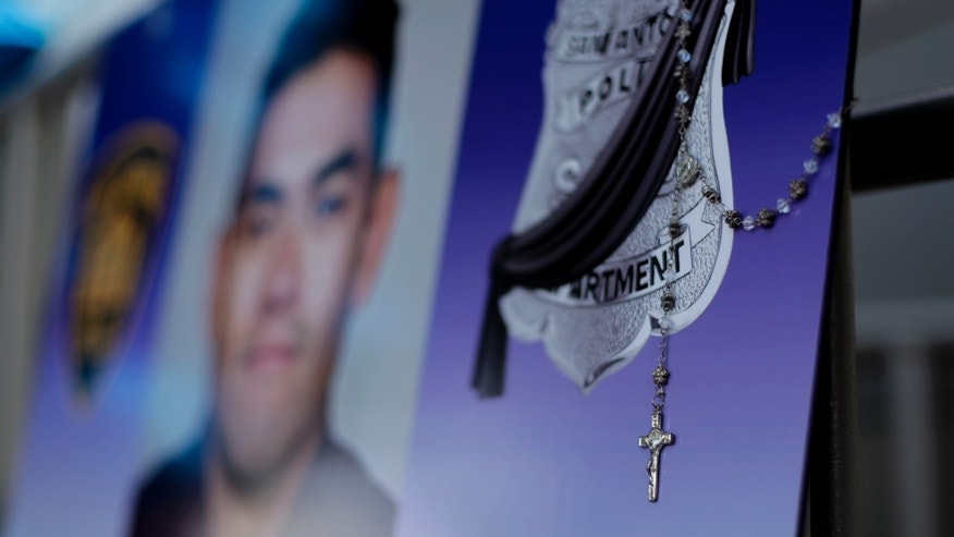 A rosary hangs on a photo of San Antonio police Officer Miguel Moreno at a makeshift memorial Friday.