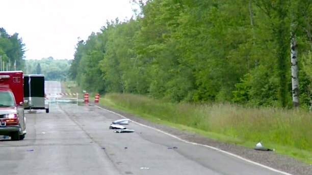 In this image made from a video provided by WAOW debris covers the road on Sunday, July, 2, 2017, near Phillips, Wis., after several people were killed in an airplane crash on Saturday. The Price County Sheriff's Office says the plane had left from Chicago and was heading to Canada on a fishing trip. (Courtesy WAOW via AP)