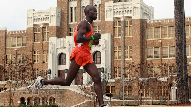 FILE - In this March 7, 2010, file photo, Moninda Marube runs past Little Rock Central High during the Little Rock Marathon race in Little Rock, Ark. Marube, of Kenya, says he had to outrun two charging bears while training in the woods Wednesday, July 5, 2017, near his home in Auburn, Maine. (AP Photo/Russell Powell, File)