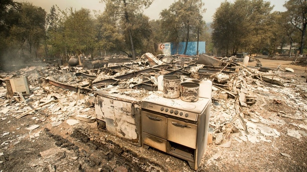 A stove stands in front of a structure leveled by a wildfire near Oroville, Calif., on Saturday, July 8, 2017. Residents were ordered to evacuate from several roads in the rural area as flames climbed tall trees. (AP Photo/Noah Berger)