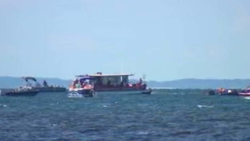 Boats full of protesters circled Minnesota Gov. Mark Dayton's boat as he tried to draw attention to the nationally recognized bass fishing in Lake Mille Lacs.