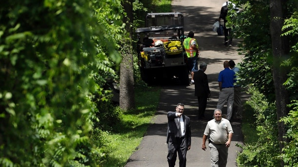 Law enforcement officials walk down a blocked off drive way, Monday, July 10, 2017, in Solebury, Pa. Authorities near Philadelphia asked for the public's help and patience Monday as they search for four young men who disappeared over the past week in what they are calling a criminal investigation. (AP Photo/Matt Slocum)