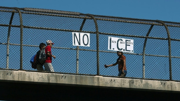 Los Angeles resident Jack Gerritsen ,81, has been making a political comment since the election of President Donald Trump by placing  NO I.C.E. (U.S.  Immigration and Customs Enforcement) signs  throughout the city, this one on a pedestrian overpass crossing a freeway in Los Angeles, California, U.S. April 18, 2017.  REUTERS/Mike Blake - RTS131NP