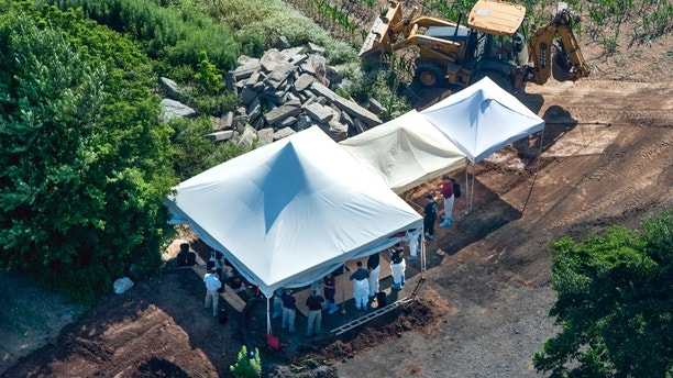 Investigators gather under tents as they search a property, Wednesday, July 12, 2017, in Solebury, Pa., for four missing young Pennsylvania men feared to be the victims of foul play. (Clem Murray/The Philadelphia Inquirer via AP)