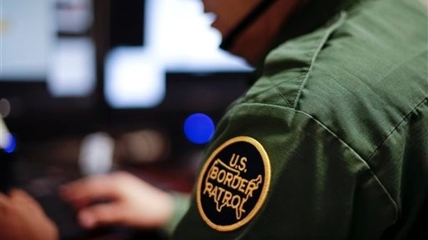 In this June 5, 2014 photo, a Border Patrol agent uses a headset and computer to conduct a long distance interview by video with a person arrested crossing the border in Texas, from a facility in San Diego. Hit with a dramatic increase of Central Americans crossing in South Texas, the Border Patrol is relieving staffing woes by enlisting agents in less busy sectors to process arrests through video interviews.  (AP Photo/Gregory Bull)