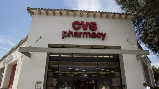 People walk outside a CVS store in Pasadena, California, August 3, 2015. REUTERS/Mario Anzuoni