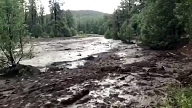 This Saturday, July 15, 2017 image from video provided by Scott Muller shows the flash flood just upstream of a popular swimming hole where it swept several people to their deaths in the Tonto National Forest near Payson, Ariz. The flood was the result of a thunderstorm that dumped heavy rainfall just upstream, unleashing 6-foot-high floodwaters, dark with ash from a summer wildfire. (Scott Muller via AP)