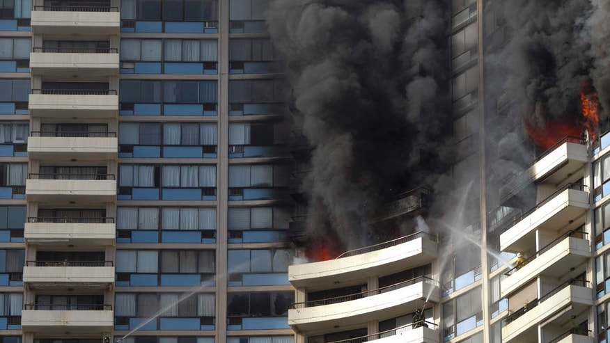 Firefighters on several balconies spray water upwards while trying to contain a fire at the Marco Polo apartment complex, Friday, July 14, 2017, in Honolulu.