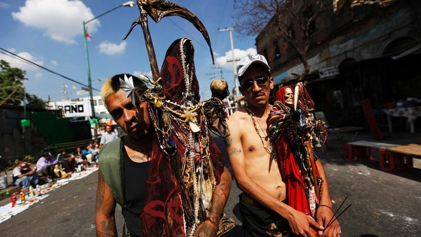 Followers of La Santa Muerte (The Saint of Death), a cult figure often depicted as a skeletal grim reaper, pose for a photograph at the saint's altar in Tepito, Mexico City January 1, 2013. Followers gather at the altar at the start of a new year, and subsequently on the first of each month, to leave offerings of apples, flowers, cigarettes, coloured candles and tequila to thank her for granted favours or to ask for new ones.   REUTERS/Claudia Daut (MEXICO - Tags: SOCIETY RELIGION) - RTR3C1F8