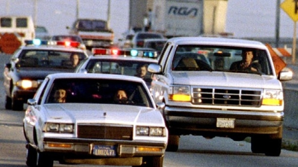 A Ford Bronco carrying O.J. Simpson (hidden in rear seat) is reportedly driven by Simpson's former teammate Al Cowlings, chased by dozens of police cars during an hour long pursuit through Los Angeles area freeways, June 17. Simpson was charged in the double murder of his ex wife and her friend by Los Angeles Police. ? QUALITY DOCUMENT - RTXFBBM