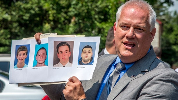 Bucks County District Attorney Matthew Weintraub holds up photos of four men who are missing during a news conference in Solebury Township, Pa., Monday, July 10, 2017. The four men, who went missing last week, are Dean Finocchiaro, from left, Tom Meo, Jimi Tar Patrick and Mark Sturgis. (Clem Murray/The Philadelphia Inquirer via AP)