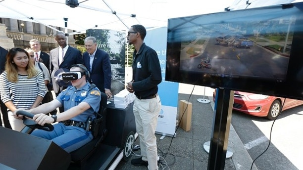 Washington State Patrol cadet Cody Fath, second from lower left, wears goggles as he views a virtual reality depiction of several distracted driving scenarios during a press event, Monday, July 17, 2017, at the Capitol in Olympia, Wash., to raise awareness of Washington state's new law prohibiting the use of nearly all phones and mobile devices while driving. The law, which is part of the Driving Under the Influence of Electronics Act, goes into effect July 23, 2017. (AP Photo/Ted S. Warren)