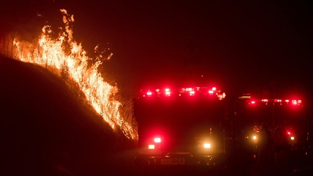 Flames from a backfire burn above fire trucks as CalFire crews battle the wildfires near Mariposa, Calif., on Tuesday, July 18, 2017.  Record rain and snowfall in the mountains this winter was celebrated for bringing California's five-year drought to its knees, but it has turned into a challenge for firefighters battling flames feeding on dense vegetation, officials said.  (AP Photo/Noah Berger)