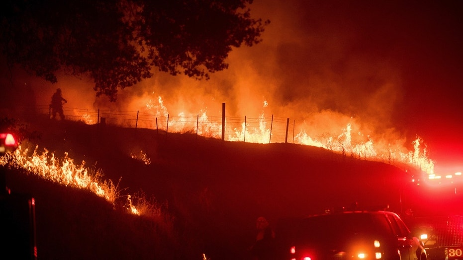 Flames from a backfire burn as CalFire crews battle the wildfires near Mariposa, Calif.