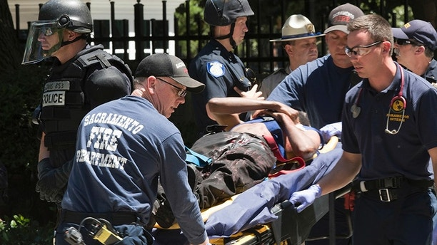 FILE - In this June 26, 2016, file photo, paramedics rush a stabbing victim to an ambulance after violence erupted during a white nationalist group's rally outside the state Capitol in Sacramento, Calif. The Sacramento County District Attorney's Office said Tuesday, July 18, 2017, that two people are being charged for alleged assault with a deadly weapon and participating in a riot. Other arrests are expected from the eight-month long investigation conducted by the California Highway Patrol. (AP Photo/Steven Styles, File)