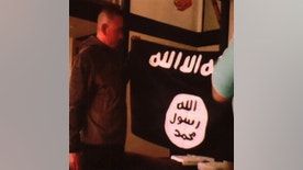 "In this image taken from FBI video and provided by the U.S. Attorney's Office in Hawaii on Thursday, July 13, 2017, Army Sgt. 1st Class Ikaika Kang holds an Islamic State group flag after allegedly pledging allegiance to the terror group at a house in Honolulu on July 8, 2017.  The active duty soldier based in Hawaii helped purchase a drone for the Islamic State group to use against American forces and said he wanted to use his rifle to ""kill a bunch of people,"" according to an FBI affidavit. A detention hearing is set for Kang on Thursday. (FBI/U.S Attorney's Office, District of Hawaii via AP)"