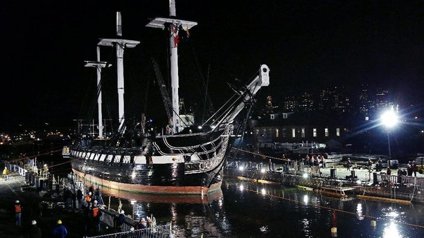 The USS Constitution is guided into a dry dock in Boston, Monday, May 18, 2015. The world's oldest commissioned warship still afloat, which was launched in 1797, will under go a major restoration project.  The project is expected to take three years to complete and as much as $15 million to complete. (AP Photo/Charles Krupa)