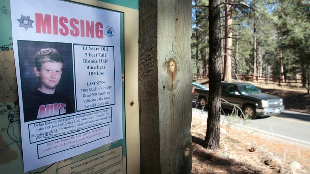 In this Nov. 26, 2012 file photo, a missing poster of 13-year-old Dylan Redwine hangs on a trail head sign next to Vallecito Reservoir in Vallecito, Colo. Police have arrested Mark Redwine for the death of his 13-year-old son, Saturday, July 22, 2017.  Mark Redwine's arrest Saturday in Bellingham, Washington, follows a grand jury indictment for second-degree murder and child abuse resulting in death. (Shaun Stanley/The Durango Herald via AP, File)