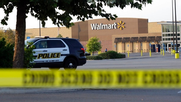 San Antonio police officers investigate the scene where eight people were found dead in a tractor-trailer loaded with at least 30 others outside a Walmart store in stifling summer heat in what police are calling a horrific human trafficking case, Sunday, July 23, 2017, in San Antonio. (AP Photo/Eric Gay)