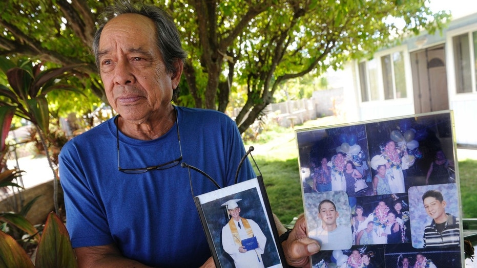 "In this July 10, 2017 photo, Clifford Kang, father of soldier Ikaika E. Kang, poses with photos of his son in Kailua, Hawaii. Ikaika E. Kang, an active-duty U.S. soldier, was arrested over the weekend on terrorism charges that accuse him of pledging allegiance to the Islamic State group and saying he wanted to ""kill a bunch of people."" Ikaika E. Kang is scheduled to appear in federal court for an arraignment Monday, July 24, 2017. (Bruce Asato/The Star-Advertiser via AP)"