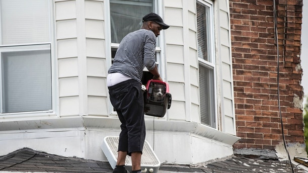 The resident of collapsed home holds his cat on the roof of the standing portion after a Red Paw Emergency Relief Team member rescued his cat on the second floor in Philadelphia, Wednesday, July 26, 2017. Philadelphia fire and rescue officials say no one was seriously injured and all residents are accounted for after escaping from a row home when a brick wall collapsed. (AP Photo/Matt Rourke)
