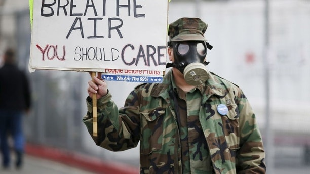 Brian Seligman holds a sign to protest a gas leak in the Porter Ranch area of Los Angeles before a meeting of the California Air Quality Management District in Granada Hills, California January 9, 2016. REUTERS/Danny Moloshok
