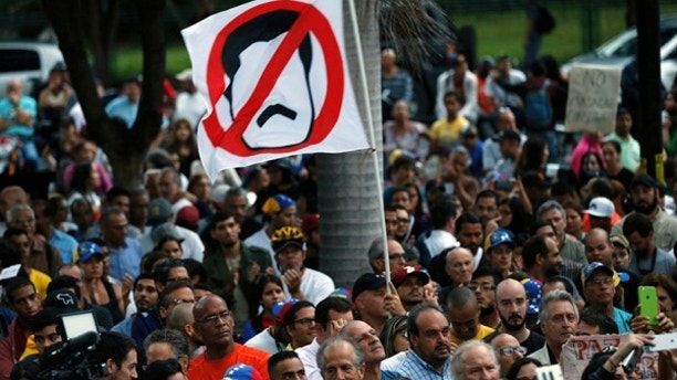 An anti-government demonstrator waves a flag against Venezuela's President Nicolas Maduro during a vigil in honor of those who have been killed during clashes between security forces and demonstrators in Caracas, Venezuela, Monday, July 31, 2017. Many analysts believe Sunday's vote for a newly elected assembly that will rewrite Venezuela's constitution will catalyze yet more disturbances in a country that has seen four months of street protests in which at least 125 people have died. (AP Photo/Ariana Cubillos)