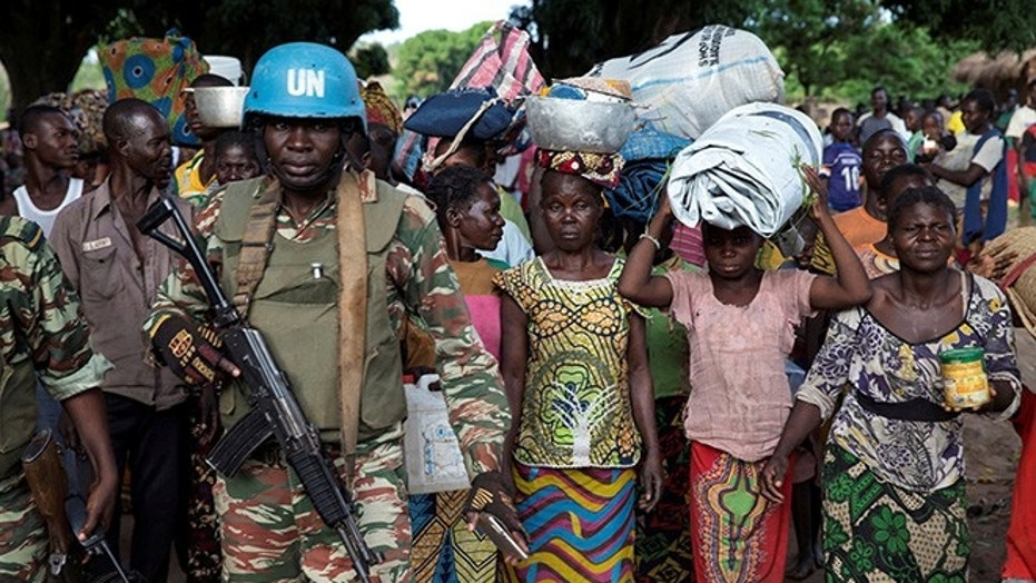 A Cameroonian United Nations peacekeeping soldier guards woman fleeing a village.