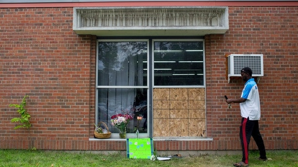 Abdul Mohamed photographs the damage outside of the Dar Al Farooq Islamic Center in Bloomington, Minn., on Sunday, Aug. 6, 2017.  An explosion damaged a room and shattered windows as worshippers prepared for morning prayers early Saturday. (Courtney Pedroza/Star Tribune via AP)