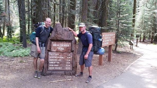 In this July 23, 2017, photo provided by Brian McKinney, Sam Vonderheide, right, and McKinney pose for a photo on the High Sierra trail in Sequoia National Park, Calif. The two hikers walking a High Sierra trail videotaped a nerve-wracking stare-down with a wild mountain lion. The video shows the adult lion scurry down a winding trail out of sight; moments later the hikers round a turn to see the large cat peering down on them from a rocky perch feet away. Wildlife biologist Daniel Gammons said the men did the right thing by staying calm. Biologists say you should make yourself appear big by waving your arms overhead and scare off the animal, as the men did. (Brian McKinney via AP)