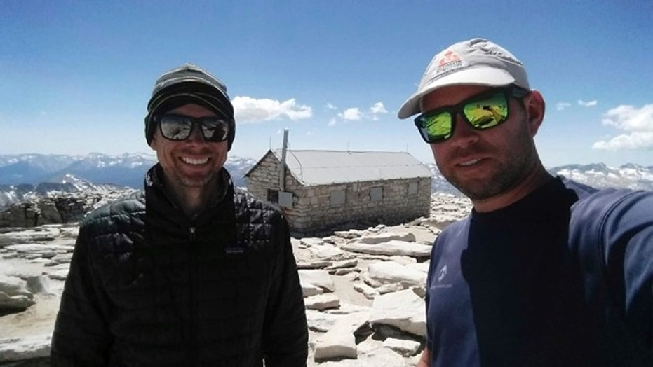 In this August 2017 photo provided by Brian McKinney, Sam Vonderheide, right, and McKinney, left, pose for a photo on the top of Mount Whitney, Calif. The two hikers walking a High Sierra trail videotaped a nerve-wracking stare-down with a wild mountain lion on July 23. The video shows the adult lion scurry down a winding trail out of sight; moments later the hikers round a turn to see the large cat peering down on them from a rocky perch feet away. (Brian McKinney via AP)