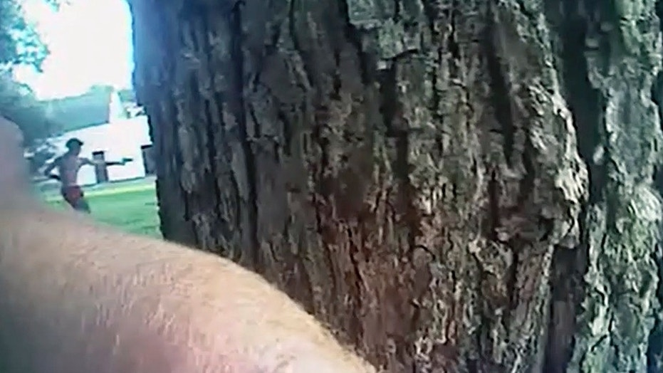 This image taken from police body camera video shows Aries Clark, 16, raising a black BB gun that looked like a handgun at officers before he was shot in Marion, Ark. July 25.