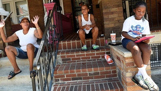 "Neighborhood residents Mary Johnson (C), her niece Erika Johnson (L) and her granddaughter Ayanna Herbert, 9, spend time near 2100 Homewood Avenue before the ""Huddle Up on the Wood"" event and Cease Fire Community Jubilee during the 72-hour community-led Baltimore Ceasefire against gun violence in Baltimore, Maryland, U.S. August 4, 2017. REUTERS/Sait Serkan Gurbuz - RTS1AFF8"