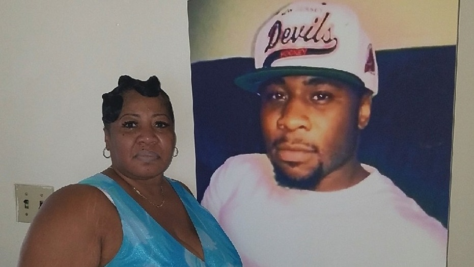 June Rodgers in front of a picture of her son Christian.