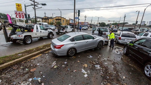 CORRECTS CREDIT TO THE ADVOCATE- Flooded cars are cleared from Orleans Avenue at Broad Street in Mid City Sunday, Aug. 6, 2017, after a deluge in the New Orleans area on Saturday caused widespread flash flooding. (Scott Threlkeld/The Advocate via AP)