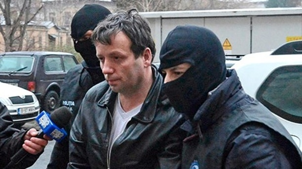 "Marcel Lehel Lazar, 40, is escorted by masked policemen in Bucharest, after being arrested in Arad, 550 km (337 miles) west of Bucharest January 22, 2014. Lehel is allegedly the hacker using the nicknames ""Guccifer"" and ""The Small Fume"" and is suspected to have broken into several e-mail accounts of various politicians and celebrities and the head of Romania's Intelligence Service George Maior. REUTERS/Mediafax/Silviu Matei"