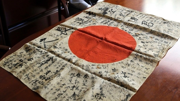 In this Monday, Aug. 7, 2017 photo, WWII veteran Marvin Strombo sits with a Japanese flag with names written on it in Portland, Ore. Strombo recovered the flag from a dead Japanese soldier in the Pacific more than 70 years ago and now, at age 93, will return the flag to the Japanese man's surviving siblings. (AP Photo/Don Ryan)
