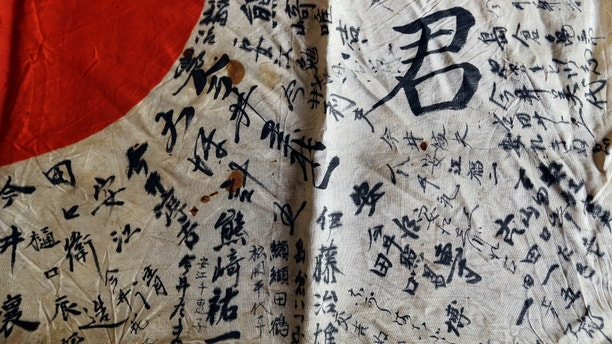 In this Monday, Aug. 7, 2017 photo, names are visible on a Japanese flag owned by WWII veteran Marvin Strombo in Portland, Ore. Strombo recovered the flag from a dead Japanese soldier in the Pacific more than 70 years ago and now, at age 93, will return the flag to the Japanese man's surviving siblings. (AP Photo/Don Ryan)