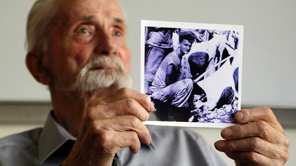 In this Monday, Aug. 7, 2017 photo, WWII veteran Marvin Strombo holds up a photo of himself taken during the battle on Saipan with him holding a captured sword and flag in Portland, Ore. Strombo recovered the flag from a dead Japanese soldier in the Pacific more than 70 years ago and now, at age 93, will return the flag to the Japanese man's surviving siblings. (AP Photo/Don Ryan)