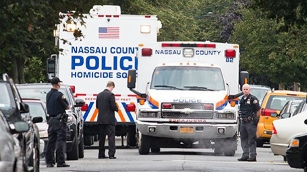 "Nassau and Hempstead police investigate the scene of a homicide in Hempstead, N.Y.,  on Saturday, Aug. 12, 2017.   Police on Long Island are searching or a ""person of interest"" in the killings of three women found inside a Hempstead home.