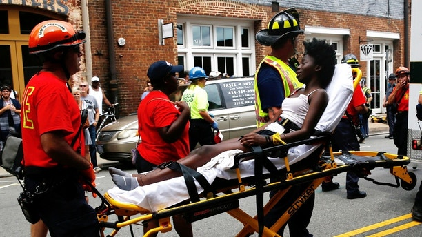 Rescue workers transport a victim who was injured when a car drove through a group of counter protestors at the