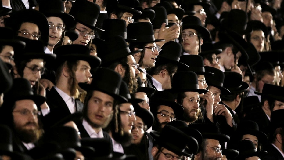 Orthodox Jews of the Satmar Hasidim crowd bleachers near a bonfire in the New York village of Kiryas Joel.