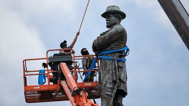 FILE- In this Friday, May 19, 2017, file photo, workers prepare to take down the statue of former Confederate Gen. Robert E. Lee, which stands over 100 feet tall, in Lee Circle in New Orleans. Lee monuments, memorials and schools in his name erected at the turn of the 20th Century are now facing scrutiny amid a demographically changing nation. Their removals are sparking heated clashes around the country just as the United States is celebrating the 150th anniversary of Reconstruction, the era when the United States tried to rebuild itself after the bloody Civil War. (AP Photo/Gerald Herbert, File)