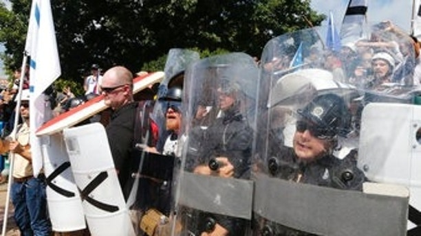 This Saturday, Aug. 12, 2017 image shows c white supremacist guarding the entrance to Emancipation Park in Charlottesville, Va. (AP Photo/Steve Helber)