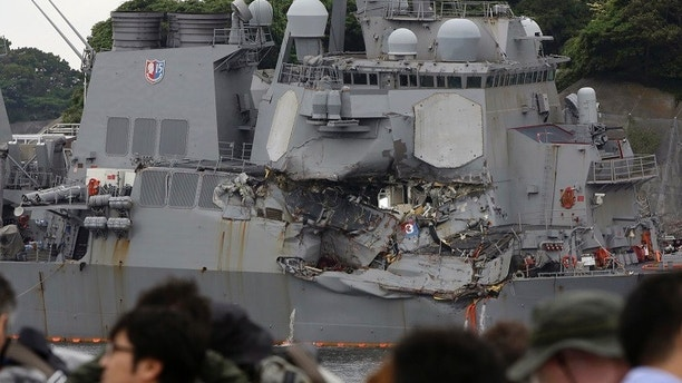 In this Sunday, June 18, 2017, file photo, journalists observe the damaged USS Fitzgerald at the U.S. Naval base in Yokosuka, southwest of Tokyo.  Navy divers found a number of sailors' bodies Sunday aboard the stricken USS Fitzgerald that collided with a container ship in the busy sea off Japan. (AP Photo/Eugene Hoshiko)