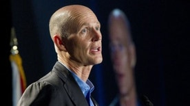 Florida Gov. Rick Scott makes a speech at the annual Governor's Hurricane Conference in Fort Lauderdale, Wednesday, May 16, 2012. Emergency managers and government officials discussed the legacy of Hurricane Andrew, which devastated South Florida 20 years ago this August, at the Conference. His televised image is shown on a nearby monitor. (AP Photo/J Pat Carter)