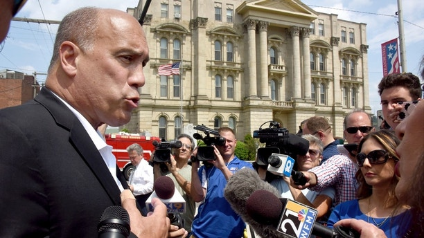City of Steubenville manager Jim Mavronatis talks to the media with the Jefferson County Courthouse in the background, in Steubenville, Ohio, Monday August 21, 2017, after Jefferson County Judge Joseph Bruzzese Jr. was ambushed and shot early Monday morning. Jefferson County Sheriff Fred Abdalla says courthouse video shows Bruzzese firing about five shots at the gunman, who also fired about five shots before a probation officer ultimately killed the suspect. (Darrell Sapp/Pittsburgh Post-Gazette via AP)