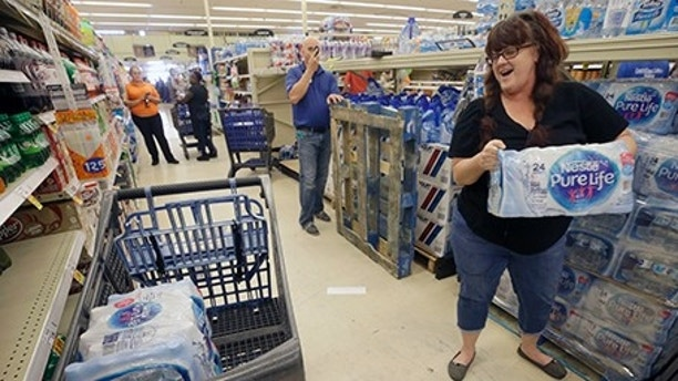 Kristy Ahrens of Galveston buys 4 cases of water at Kroger, 5730 Seawall Blvd., Thursday, Aug. 24, 2017, in Galveston, Texas as shoppers prepare for Hurricane Harvey. Harvey intensified into a hurricane Thursday and steered for the Texas coast with the potential for up to 3 feet of rain, 125 mph winds and 12-foot storm surges in what could be the fiercest hurricane to hit the United States in almost a dozen years. (Melissa Phillip/Houston Chronicle via AP)