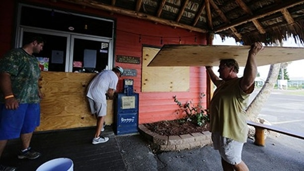 Mac Owens, left, Mark Jones, center, and Kelly Owens, right, board up their business in preparation for Hurricane Harvey, Thursday, Aug. 24, 2017, in Port Aransas, Texas. Harvey intensified into a hurricane Thursday and steered for the Texas coast.  (AP Photo/Eric Gay)